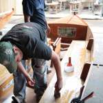 Craftsmen brush a final coat of epoxy on an 18-foot sailboat.