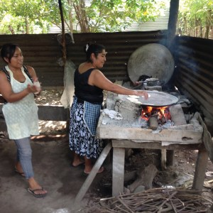 A woman uses a steel plancha over an open fire to make tortillas in the traditional method.