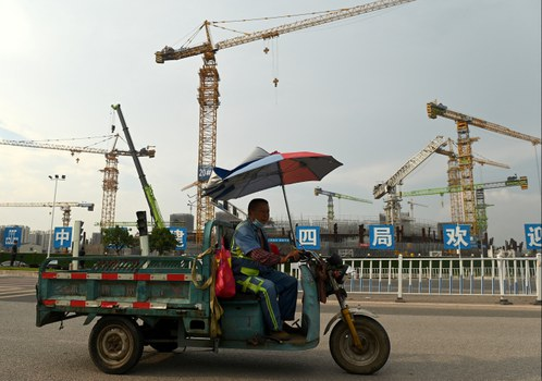 A worker commutes in front of the under-construction Guangzhou Evergrande football stadium in Guangzhou, China's southern Guangdong province, Sept. 17, 2021. Credit: AFP