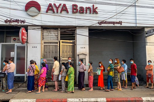 People wait for a branch of the AYA Bank to open in Yangon, April 12, 2021. AFP
