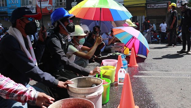 myanmar-protesters-water-buckets-tear-gas-yangon-mar1-2021.jpg