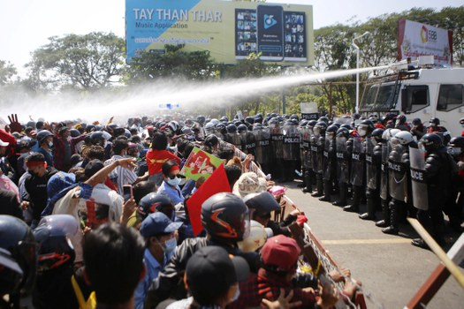 Police fire water cannons at protesters as they demonstrate against the military coup in the capital Naypyidaw, Feb. 9, 2021. AFP