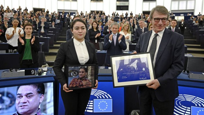 Lawmakers applaud as European Parliament President David-Maria Sassoli (R) stands next to Jewher Ilham (L), daughter of Uyghur economist and human rights activist Ilham Tohti, as she holds a photo of her father during the award ceremony for the 2019 Sakharov Prize at the European Parliament in Strasbourg, eastern France, Dec. 18, 2019.