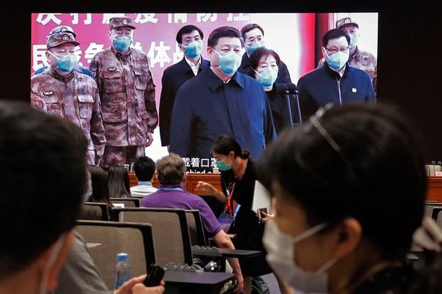 2020年6月7日,记者在屏幕旁,屏幕上显示习近平通过视频在湖北省武汉火神山医院指挥中心与患者和医务人员进行视频对话。(AP)