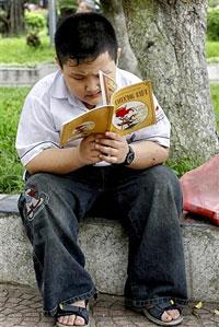 Cậu bé đọc sách tại công viên ở Hà Nội hôm 9-8-2007. AFP PHOTO