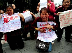 Những dân oan ức quỳ khóc khiếu nại trước Tòa án  thành phố Trùng Khánh,  phía Tây Nam Trung Quốc năm 2010. AFP