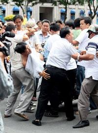 Một người đàn ông bị công an mặc thường phục bắt trong lúc đang tuần hành phản đối Trung Quốc tại SG hôm 12/6/2011. Photo by Quang Dư