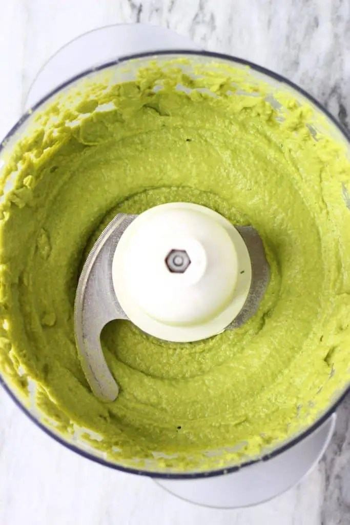 Edamame pesto in a food processor against a marble background