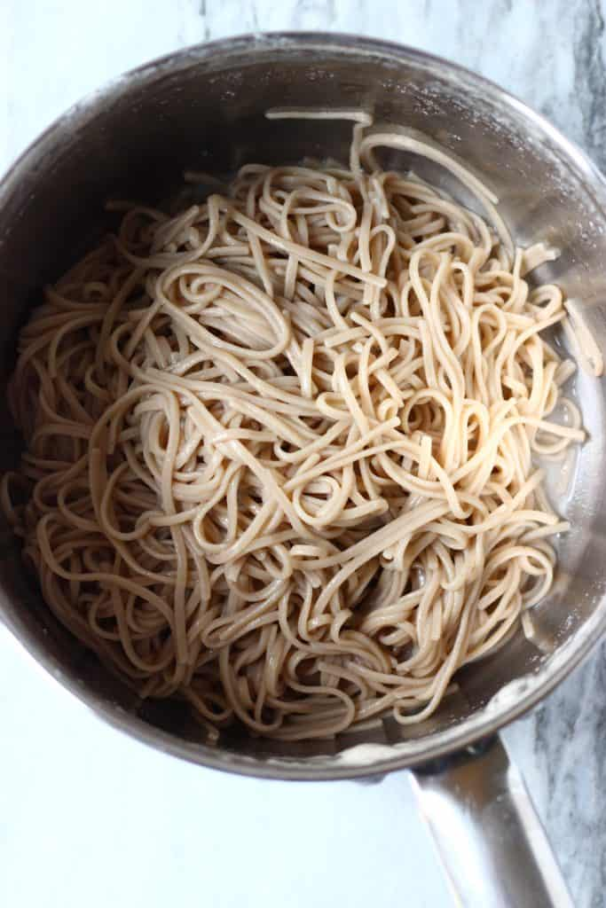 Cooked soba noodles in a silver pan against a marble background