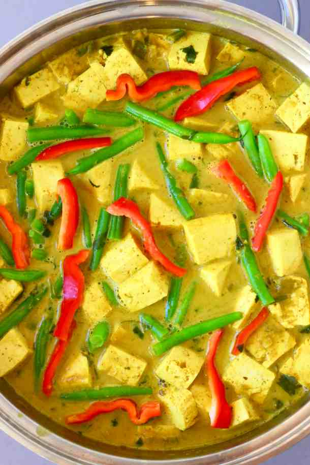 Photo of cubes of tofu, green beans and strips of red pepper in a yellow curry sauce in a silver pan