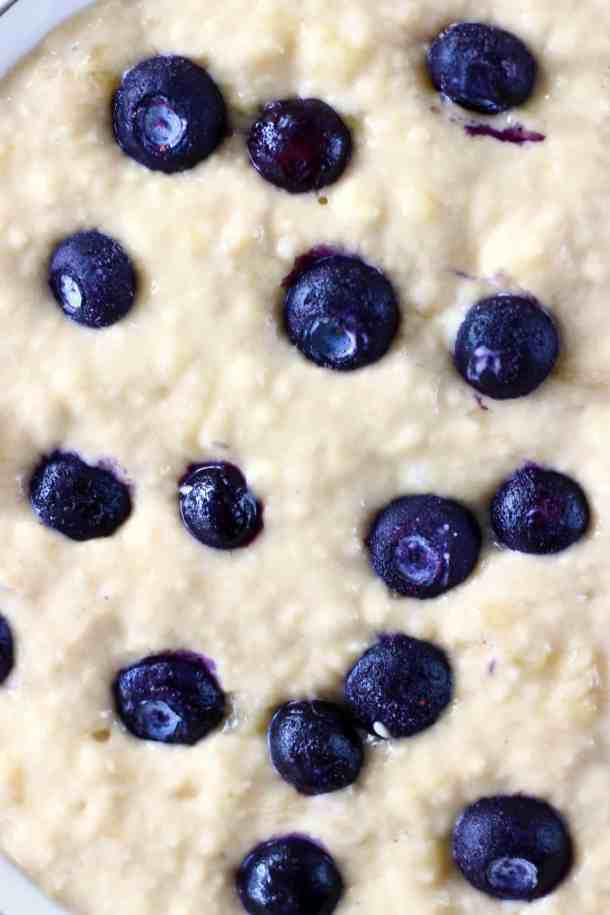 Photo of yellow cake batter dotted with fresh blueberries in a large bowl taken from above