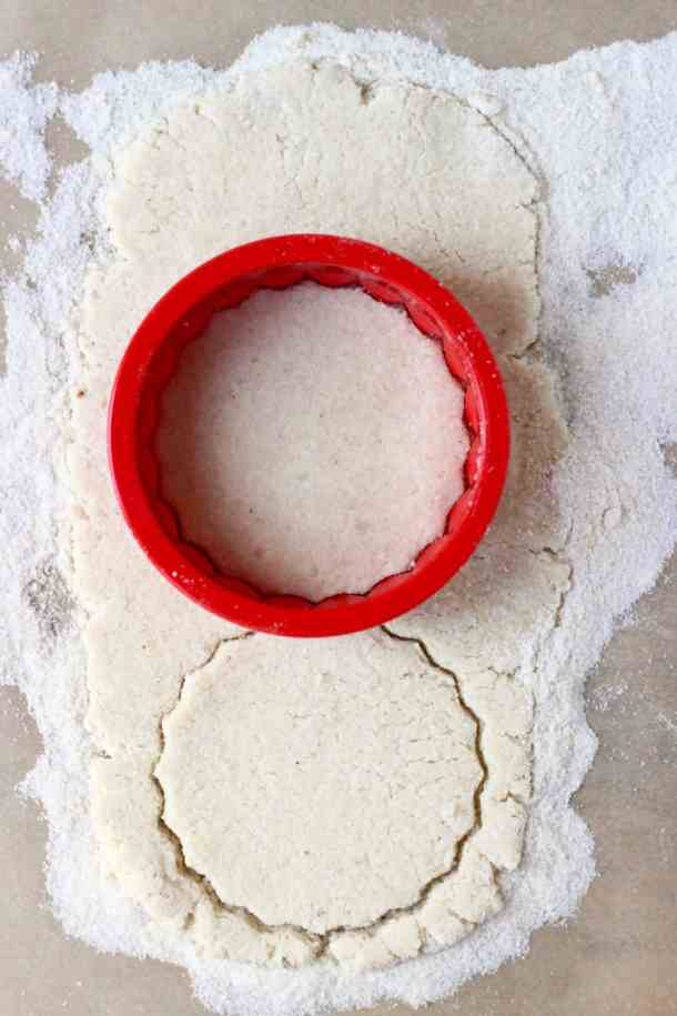 Photo of a sheet of white pastry dough with a red circular cookie cutter on it