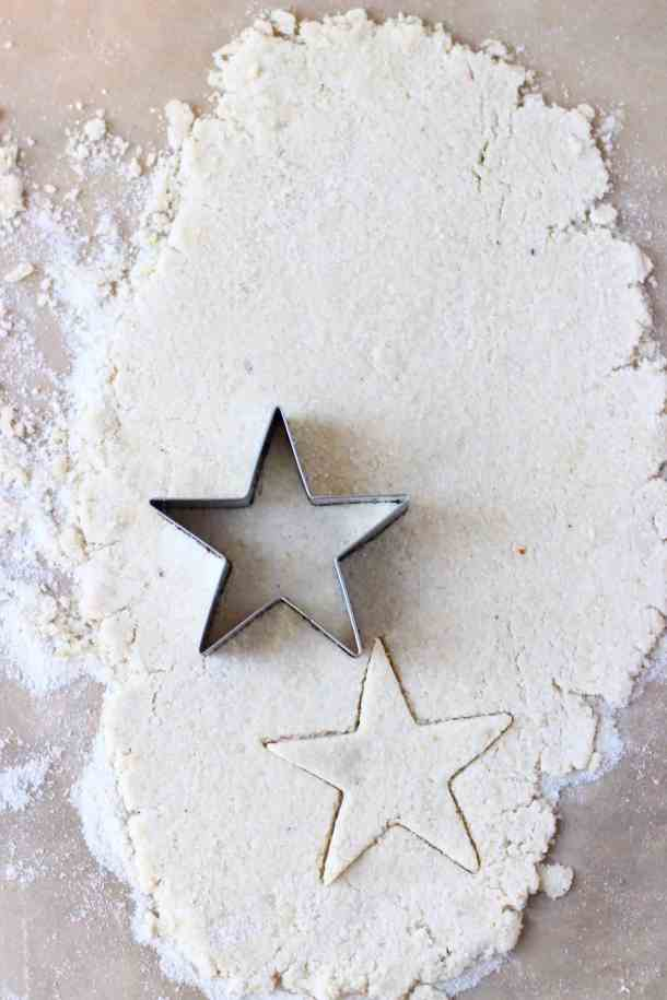 Photo of pastry dough rolled out on a piece of brown baking paper with a silver star-shaped cookie cutter cutting out star shapes