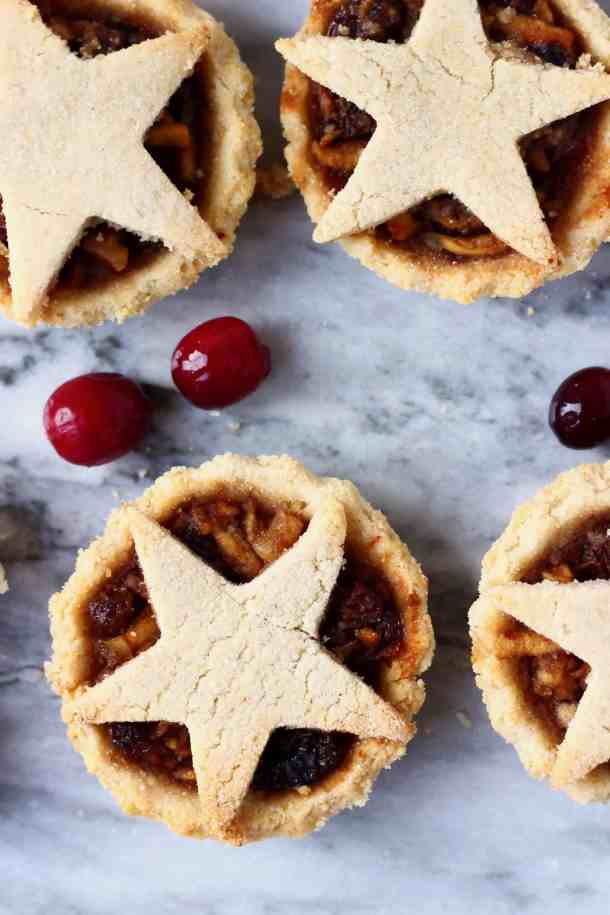 Photo of four mince pies topped with pastry stars against a marble background scattered with fresh cranberries