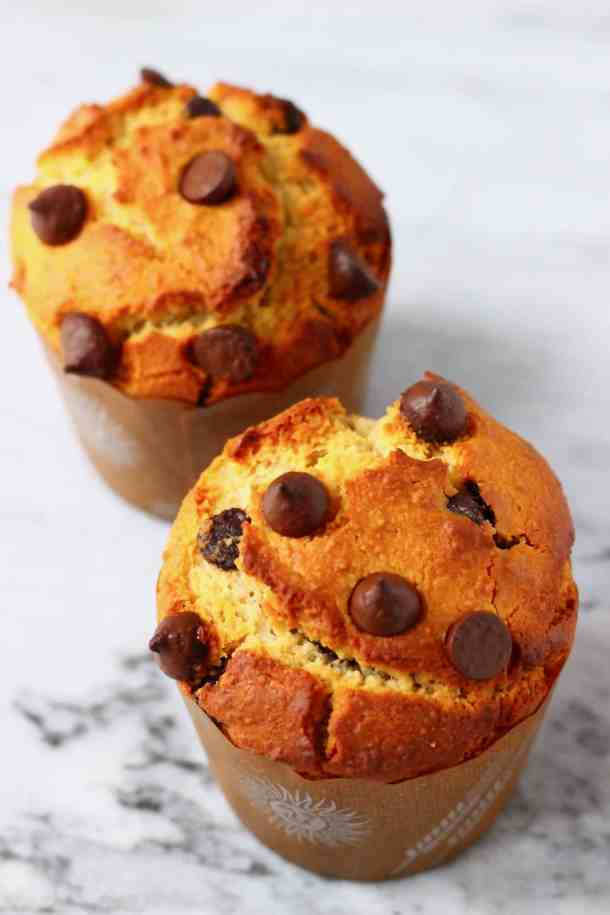 Two chocolate chip muffins in brown muffin cases against a marble background