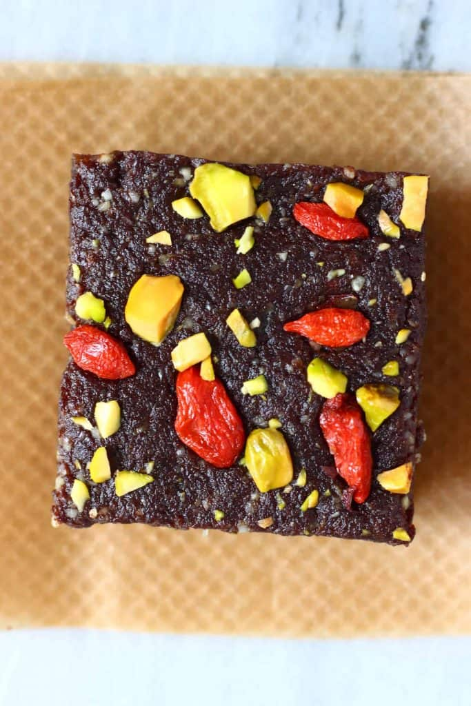 A square chocolate brownie topped with goji berries and chopped pistachios on brown baking paper against a marble background