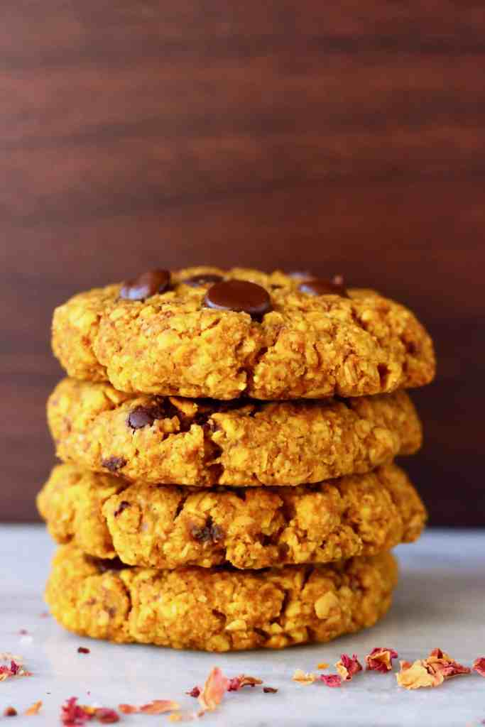 A stack of four orange pumpkin cookies studded with chocolate chips on a marble slab against a dark brown background