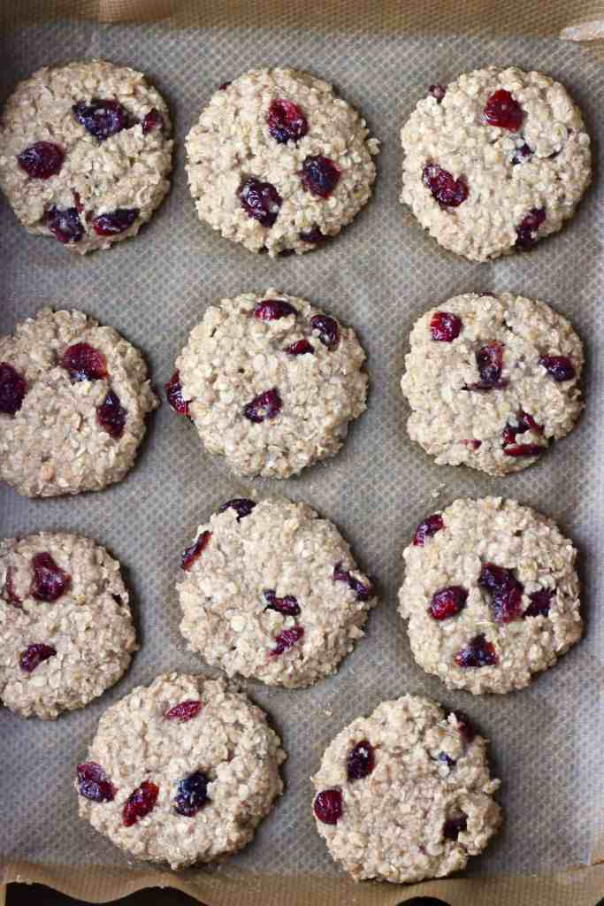11 raw oatmeal cookies with dried cranberries on brown baking paper