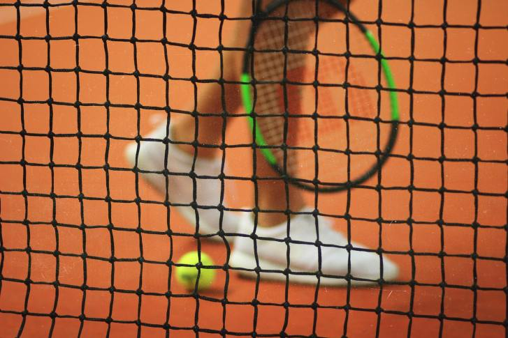 A Person's Feet in White Shoes Behind a Tennis Net | RhodesPT.net