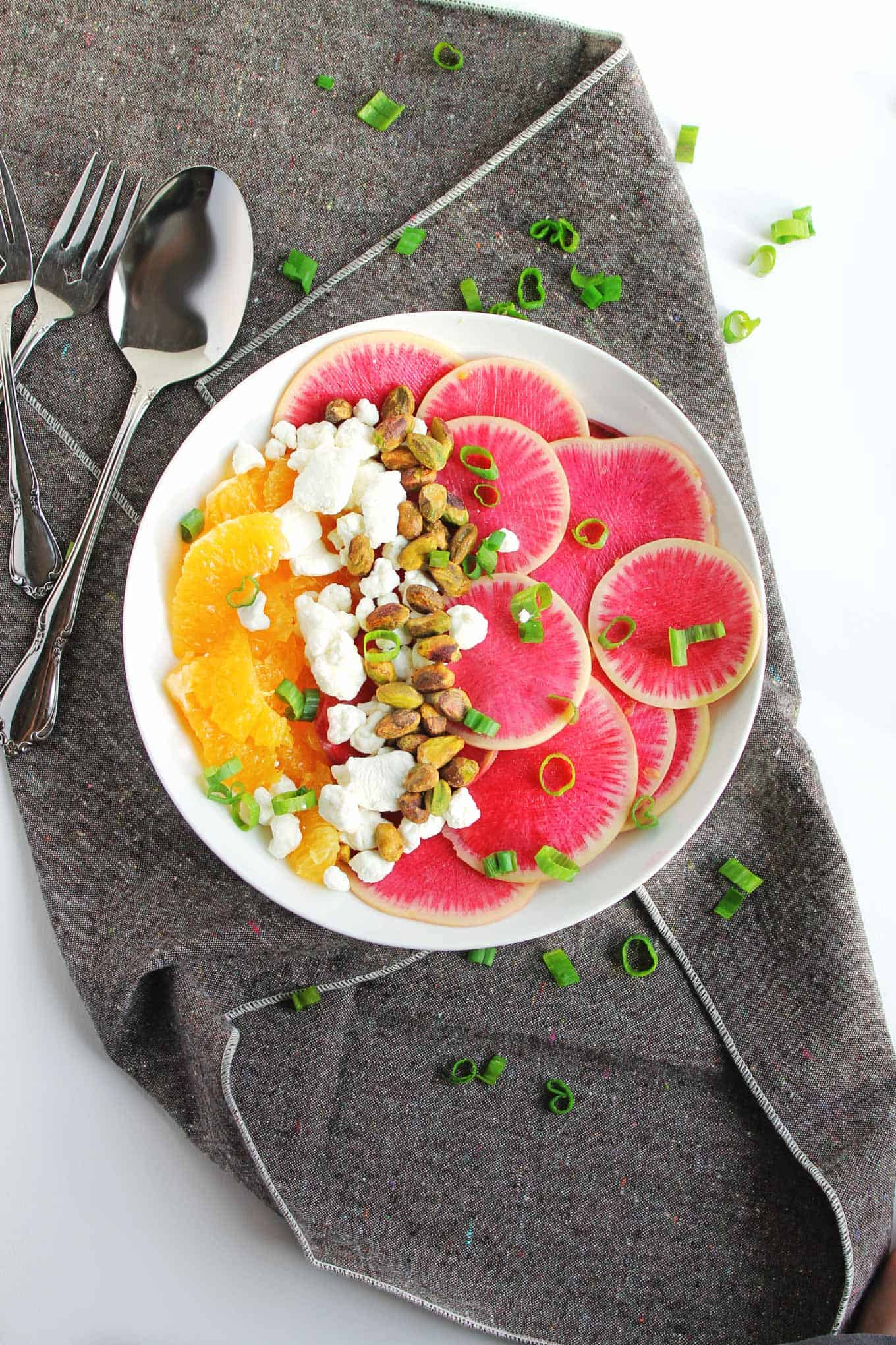 An absolutely gorgeous, simple salad! This watermelon radish orange salad with goat cheese and pistachios is bright, crunchy, and full of flavor. The perfect, colorful side dish for your table. Vegetarian, gluten free, delicious!