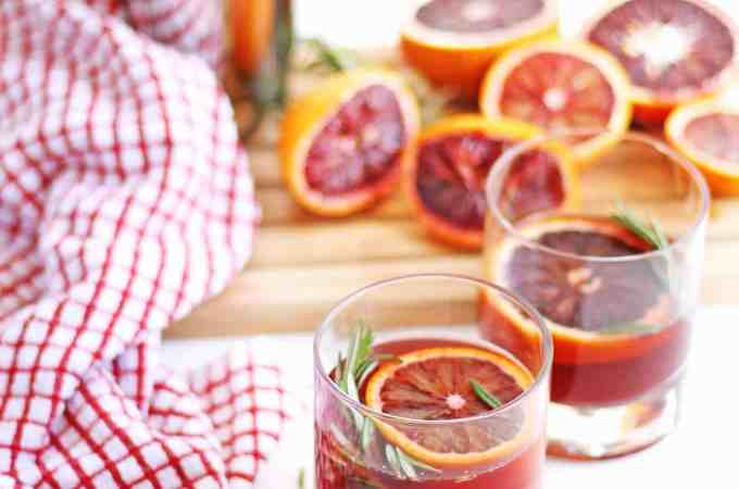 Dangerously delicious blood orange rosemary gin cocktail recipe! Fresh squeezed blood orange juice combined with fresh rosemary make this the perfect winter or spring cocktail. Gorgeous! // Rhubarbarians