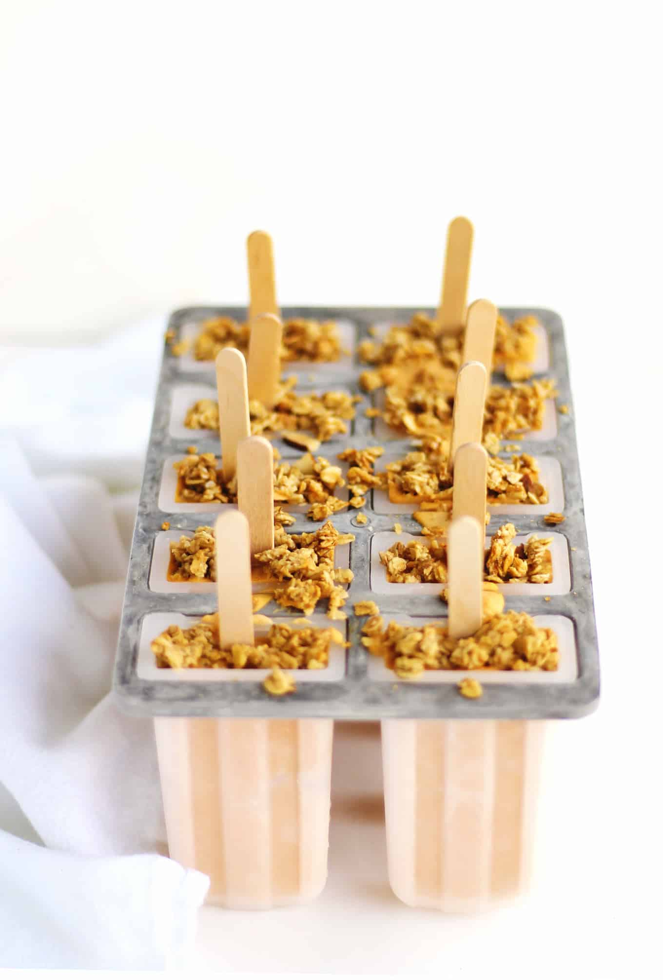 Healthy pumpkin cheesecake breakfast popsicles recipe! These parfait pops blend yogurt, pumpkin puree, pumpkin pie spice, and granola to make a creamy, autumn breakfast. YUM! // Rhubarbarians //