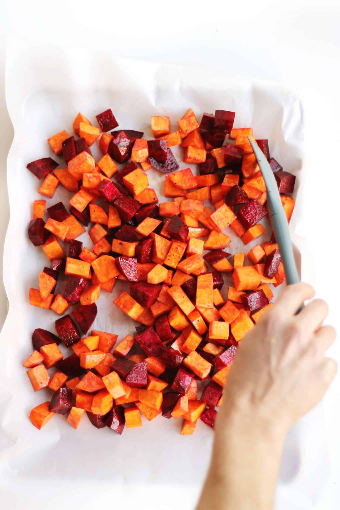 Sweet potatoes and beets on a baking pan