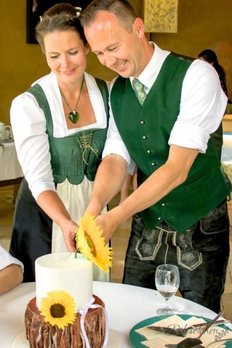 Hochzeitspaar schneidet die Hochzeitstorte (Baumstammtorte) an