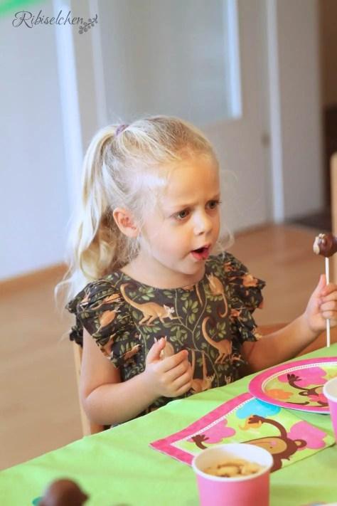 Kind isst einen Cake Pop bei der Dschungelparty
