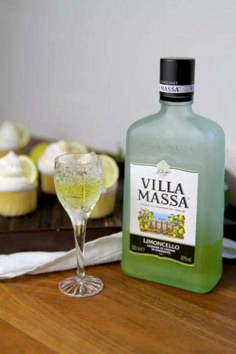 Limoncello Flasche mit Glas, im Hintergrund Cupcakes