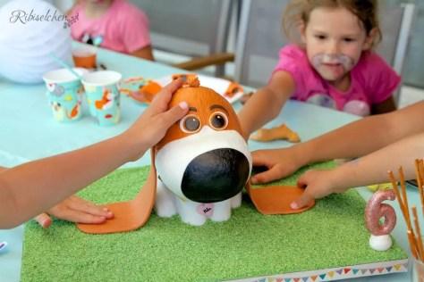 die Kinder beim Kindergeburtstag streicheln die Hundetorte
