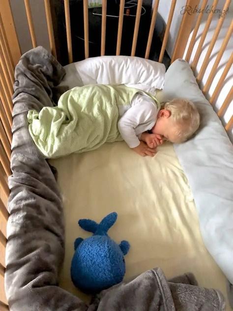 Baby in Gitterbett