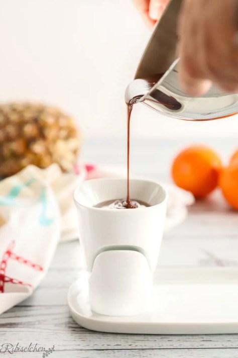 Flüssige Schokolade wird in das Schokofondue-Set gegossen
