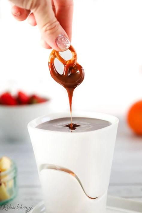 Eine Salzbrezel wird in die flüssige Schokolade getunkt