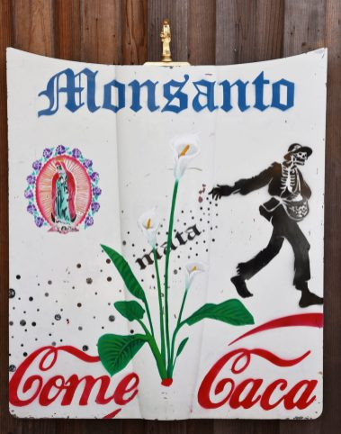 "Monsanto Come Caca, 2016, Corvette 1964 fiberglass hood, acrylic stencil with Krylon spray paint with Santo Muerto, icon statue, 54"" X 42"""