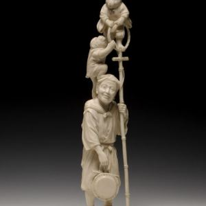 JAPANESE IVORY OKIMONO OF AN ENTERTAINER AND MONKEYS