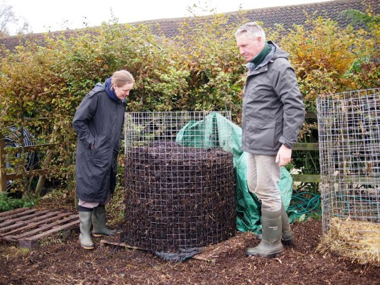 "Nigel and Joanne inspecting an ""in progress"" compost heap. The tarp used to cover and surround the heap has been pulled off so we could take a look."