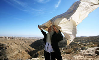 Rabbi Menachem Froman casts his talit to the winds amidst the Judean hills (Rita Castelnuovo/NY Times)