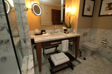 St Pancras Hotel guest bathroom - vanity with marble floor, tiling and shower/bath