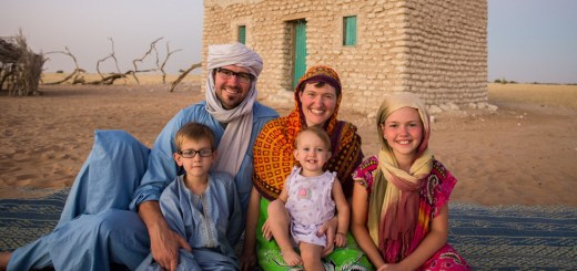 Image of a family sitting in front of a desert house in a small village in northern Chad