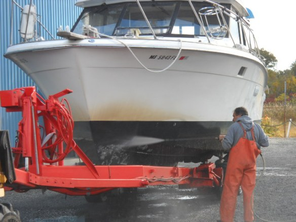 """Power-washing the bottom. Note Ginger Lees """"cruisers moustache"""", Considered a badge of honor by other cruisers."""