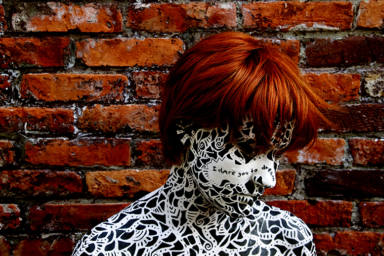 Photo called Poetica II showing a female face and shoulder bodypainted with black particles and texts, made by Veerle Ritstier