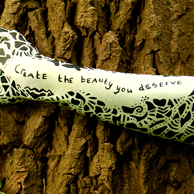 Photo called Poetica VIII showing a female arm bodypainted with black particles and texts, made by Veerle Ritstier