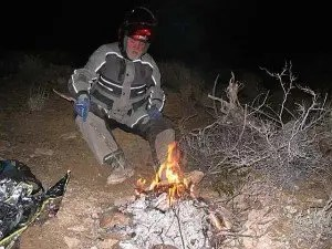 Gary Miller nurses a makeshift fire that he and Bill Dragoo built to survive an unexpected night in the desert. The fire is built out of mesquite twigs.