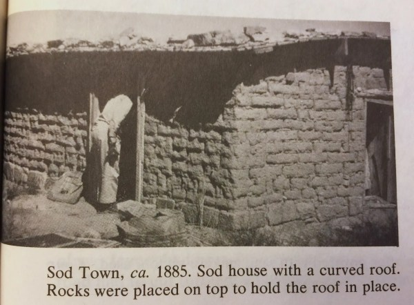 Sod Town, ca. 1885. Sod house with a curved roof. Rocks were placed on top to hold the roof in place.