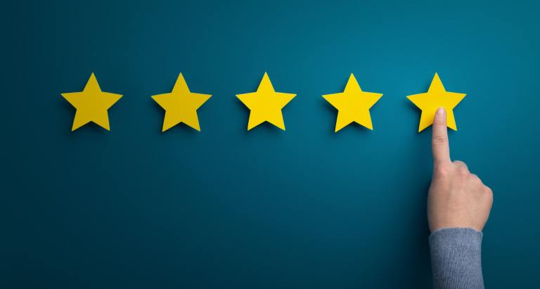 Woman hand point at five star rating on green background