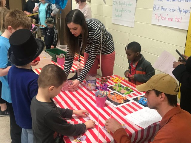 Children with two teachers at a table with math games