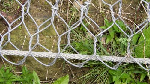 The steel cable holds the rock netting securely in place.
