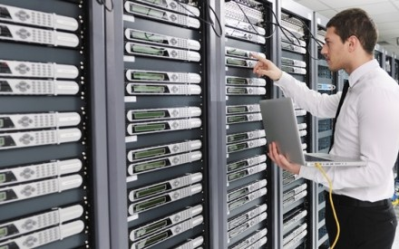 man inspecting server racks in a data centre