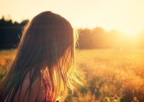 young girl looking out to a field lit by natural sunlight
